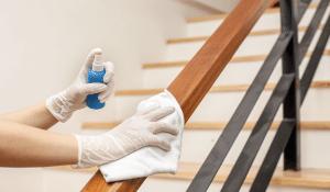Person sanitizing a hand rail
